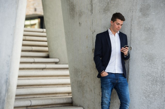young man reads a mesage on his mobile